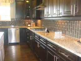 l shaped cabinetry with black granite countertop with grey mosaic