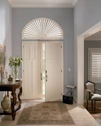 sunburst plantation shutters cover the window over the front door
