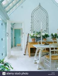metal ogee trellis on wall above sideboard in white conservatory