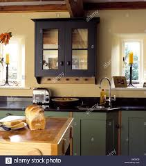 glass fronted wall cupboard above dualit toaster on black granite
