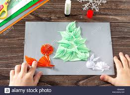 the child makes a paper christmas tree snow fox and hare