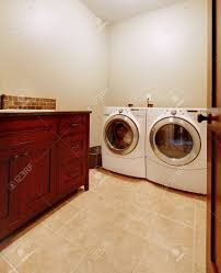 simple new laundry room with new washer and dryer and wood cabinet