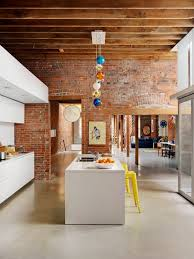 exposed brick wall lighting white cabinets drawers island with solid countertop yellow bar