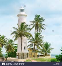 lighthouse and palm trees in the town of galle sri lanka stock