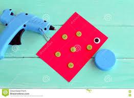 glue gun a cap from a plastic bottle buttons cardboard