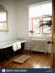 Bath Mat Wood Roll Top Bath In White Bathroom With Stained Glass Window Above