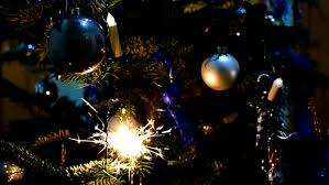 two sparklers glow on a christmas tree first is glowing already