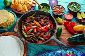 cuisine mexicaine fajitas fajitas de boeuf dans une casserole avec des sauces chili et côtés