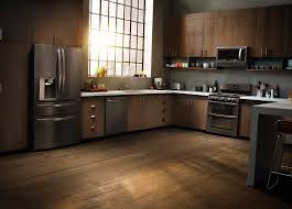 light brown kitchen cabinets with black appliances in the kitchen black is the new black