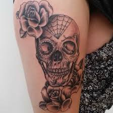 flowers and sugar skull on thigh