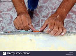 closeup view of peoples hands doing arts and crafts ceramic tile