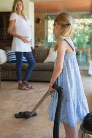 little vacuuming pregnant mother in background stock photo