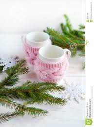 christmas tree and cup of tea in knitted cup holder on white