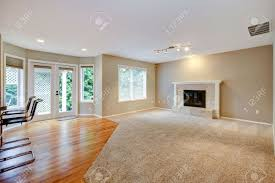 large bright empty new living room with fireplace and beige carpet large bright empty new living room with fireplace and beige carpet stock photo 15960584