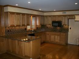kitchen backsplash with black countertops and oak cabinets