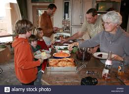family serving themselves thanksgiving dinner buffet style at home
