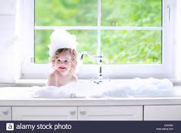 pretty verry young boys washing hairs child taking bath little baby in a kitchen sink washing hair with