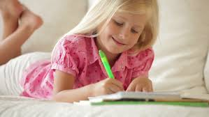 Cheerful Little Girl Lying On Sofa Writing In Notebook And Smiling - Lying sofa 2