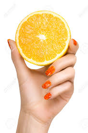 woman with trendy orange nails holding up a luscious yellow lemon