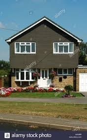 small house with garage detached house with garage and front open plan garden drive