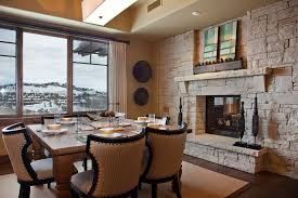 dining room stone fireplace with ceiling beams and staircase