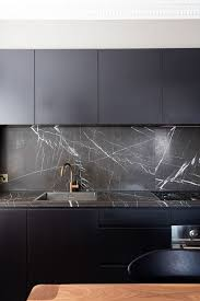 black kitchen cabinets with marble countertops a black cabinet with black marble countertops and a copper