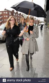 katherine jenkins braves the rainy weather as her assistant holds