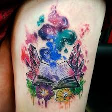 watercolor open book with flowers tattoo on thigh by joanne baker