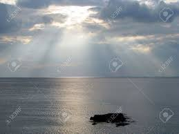 sun shining through clouds the sea stock photo picture and