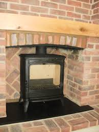 brick surround with wooden beam and wood burner fireplace and design