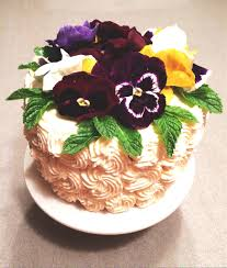 triple lemon layer cake with edible flowers buttered side up
