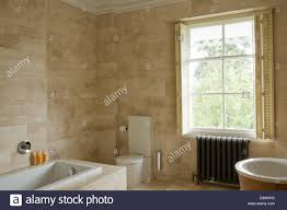 plantation shutters on window above radiator in modern bathroom