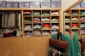 male walk in wardrobe with shirts pants belts and drawers stock