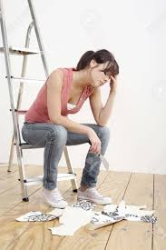 woman sitting on ladder holding a wallpaper stripper stock photo