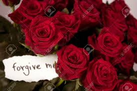 a bunch of roses in glass vase with note forgive me stock photo