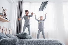 glückliche kinder die im weißen schlafzimmer spielen