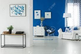 blaue wand im weißen wohnzimmer mit sofa und modernen möbeln
