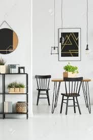 len über esstisch mit klassischen stühlen im weißen esszimmer mit poster und spiegel an der wand