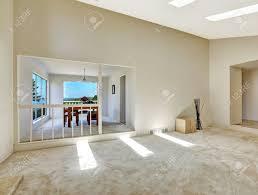 grundriss in leeres haus schönes wohnzimmer mit gewölbter decke und oberlichter blick auf leuchtend essbereich hinter dem geländer
