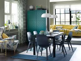 A Blue Brown And Green Dining Room Setting With Yellow Sofa In The Background