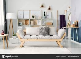 beige sofa in bright scandi living room interior with posters on a shelf between white l and ladder 200652518