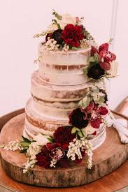 Semi Naked Wedding Cake With Trailing Red Carnations And Burgundy Orchids On A Rustic Wood Round