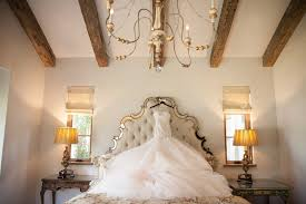 Monique Lhuillier Wedding Dress Hanging Up On Ornate Headboard In Rustic Bridal Suite With Wood Beam