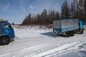 Two Trucks In Tandem On The Snowy Slope. Winter Road In The ...