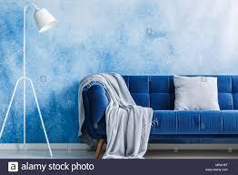 navy blaues sofa mit decke und kissen le auf einer ombre