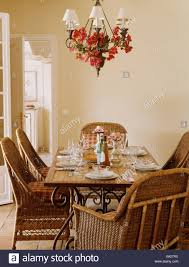 Wicker Chairs And Tile Topped Table Below Chandelier With White Shades In Traditional French Country Dining Room