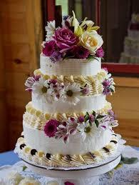 Three layer wedding round white cake with fresh roses daisies and white chocolate cream JPG