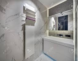 modernes badezimmer mit hellen fliesen an den wänden und auf dem boden es gibt ein weißes waschbecken mit einem verchromten wasserhahn und einen