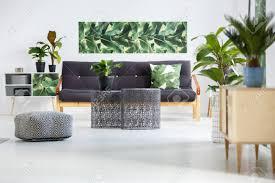 hocker neben metall tische vor dunklen sofa mit grünem kissen im wohnzimmer interieur mit pflanzen auf schränke und poster auf der wand