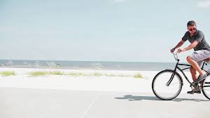 A Couple Riding Bikes At The Beach Stock Video Footage